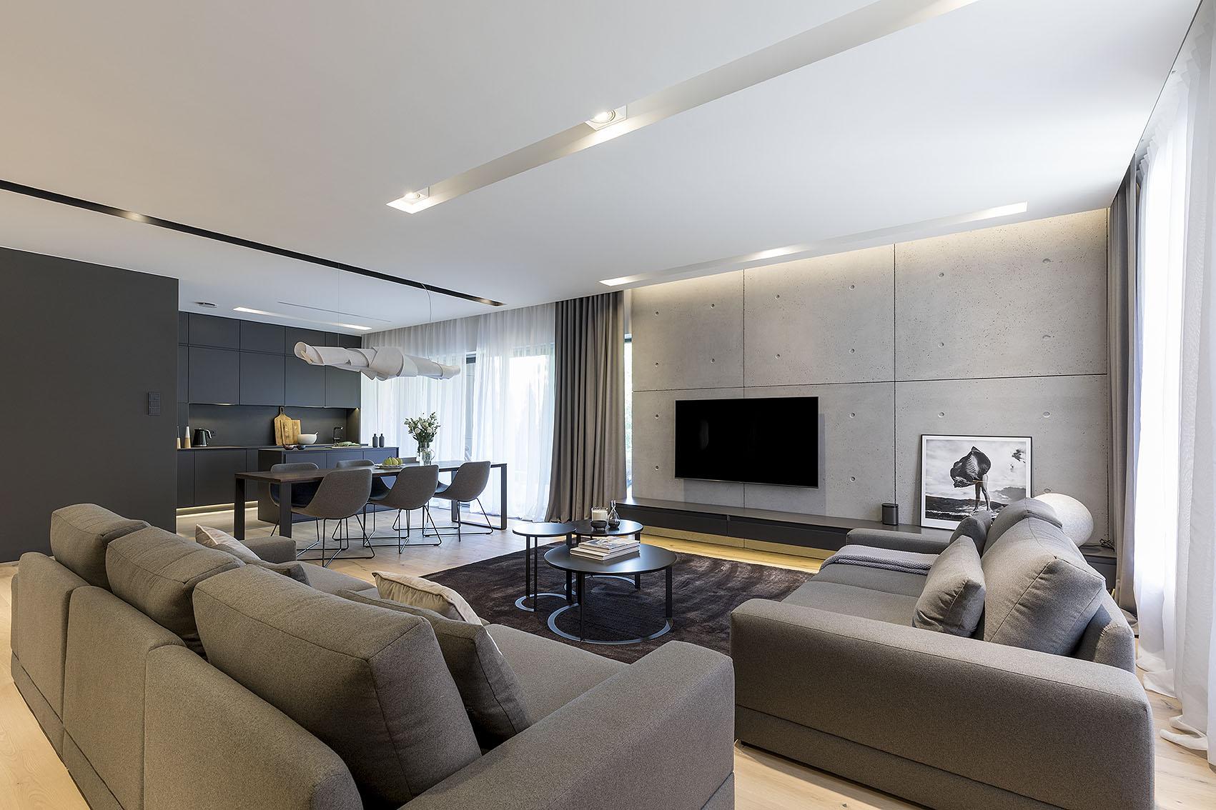Widok na salon w którym na ścianie wiszą płyty z betonu architektonicznego. Telewizor wisi nad szafką RTV. Duże szare miękkie sofy po środku których stoją stoliki kawowe na dywanie. Widok na kuchnię i jadalnię.