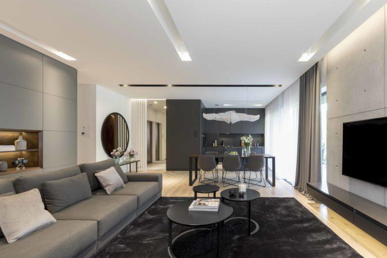 Projekt salonu z miękkimi kanapami, okładziną ściany z betonu architektonicznego na której wisi telewizor z szafką AV. Widok na jadalnię, kuchnię z wyspą, okrągłe lustro.