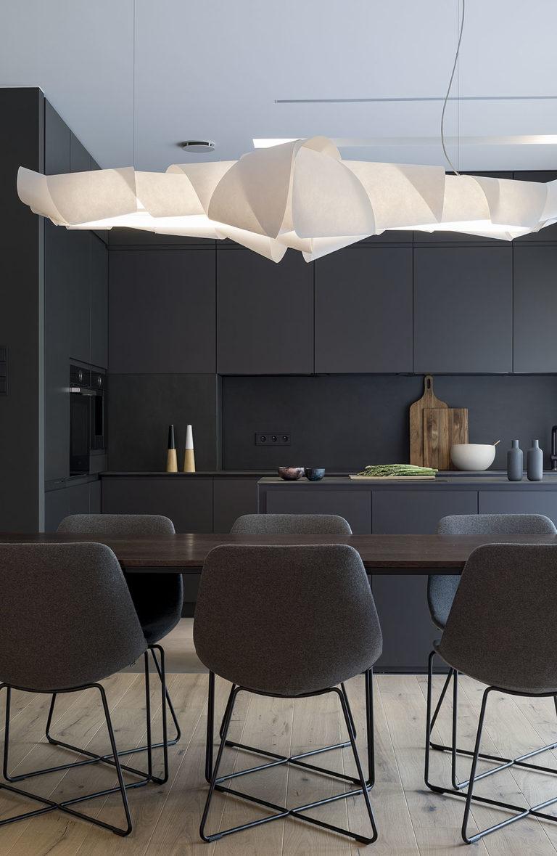 Projekt wnętrza czarnej ciemnej kuchni z wyspą oraz jadalnia z drewnianym stołem nad którym wisi dekoracyjna lampa.