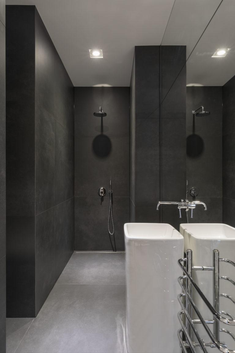 Czarna łazienka dla gości z umywalką wolnostojącą oraz baterią podtynkową. Prysznic walk in w wykończeniu chrom.