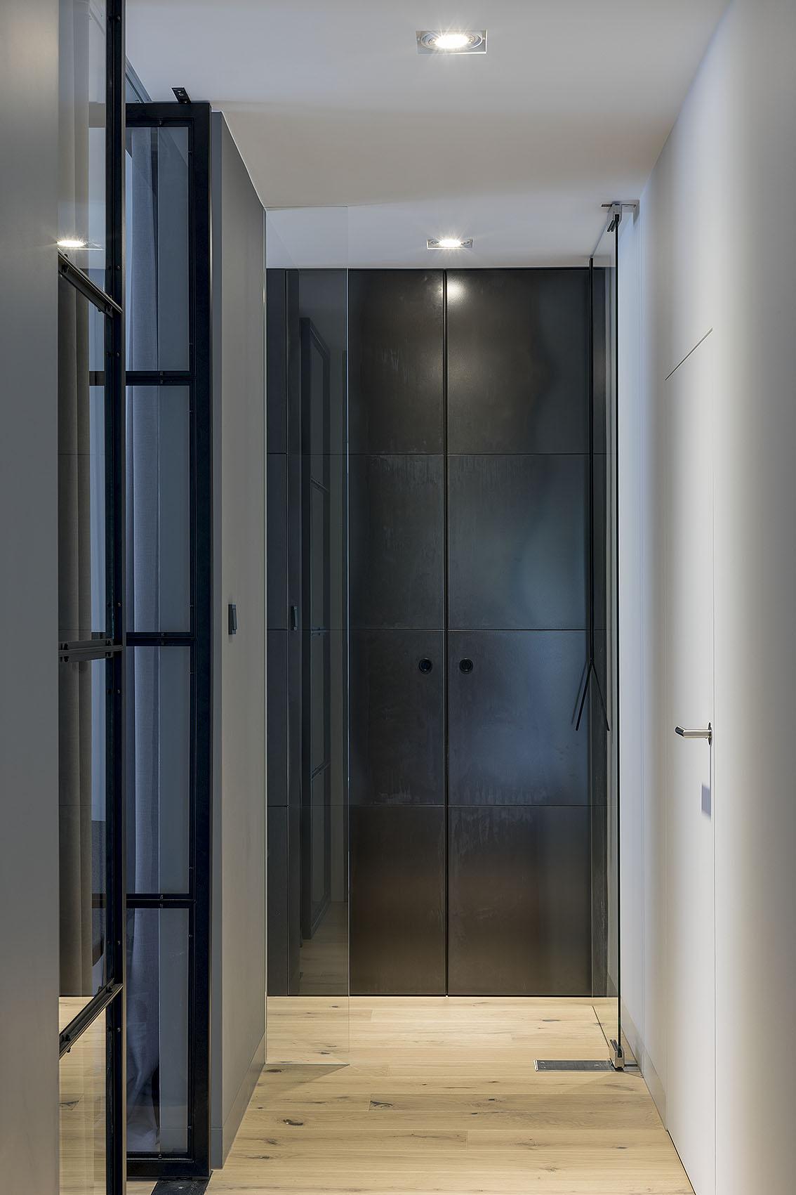 Widok na korytarz na końcu którego znajduje się szafa z frontem z blachy gorącowalcowanej, drewniana podłoga oraz drzwi ukryte do pralni