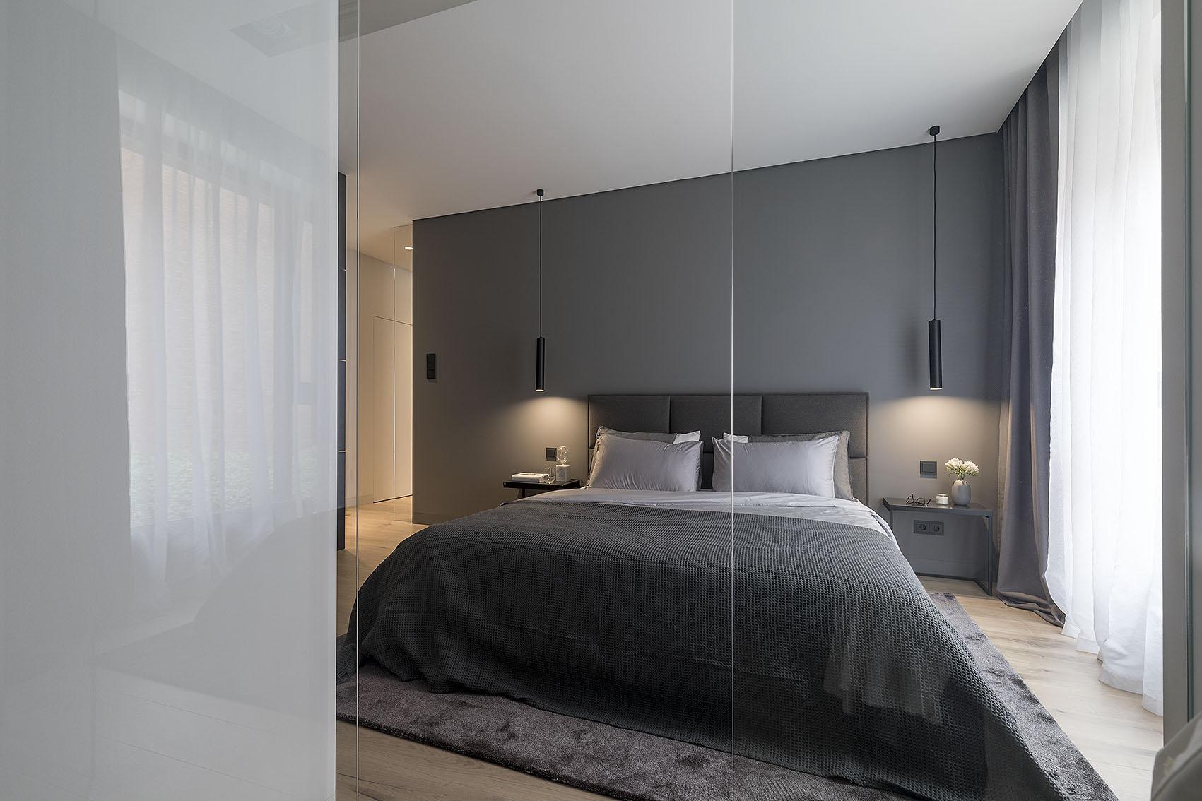 Wnętrze sypialni w szarościach, stoliki nocne oświetlone zwieszonymi lampami, narzuta przykrywająca łóżko stojące na dywanie.