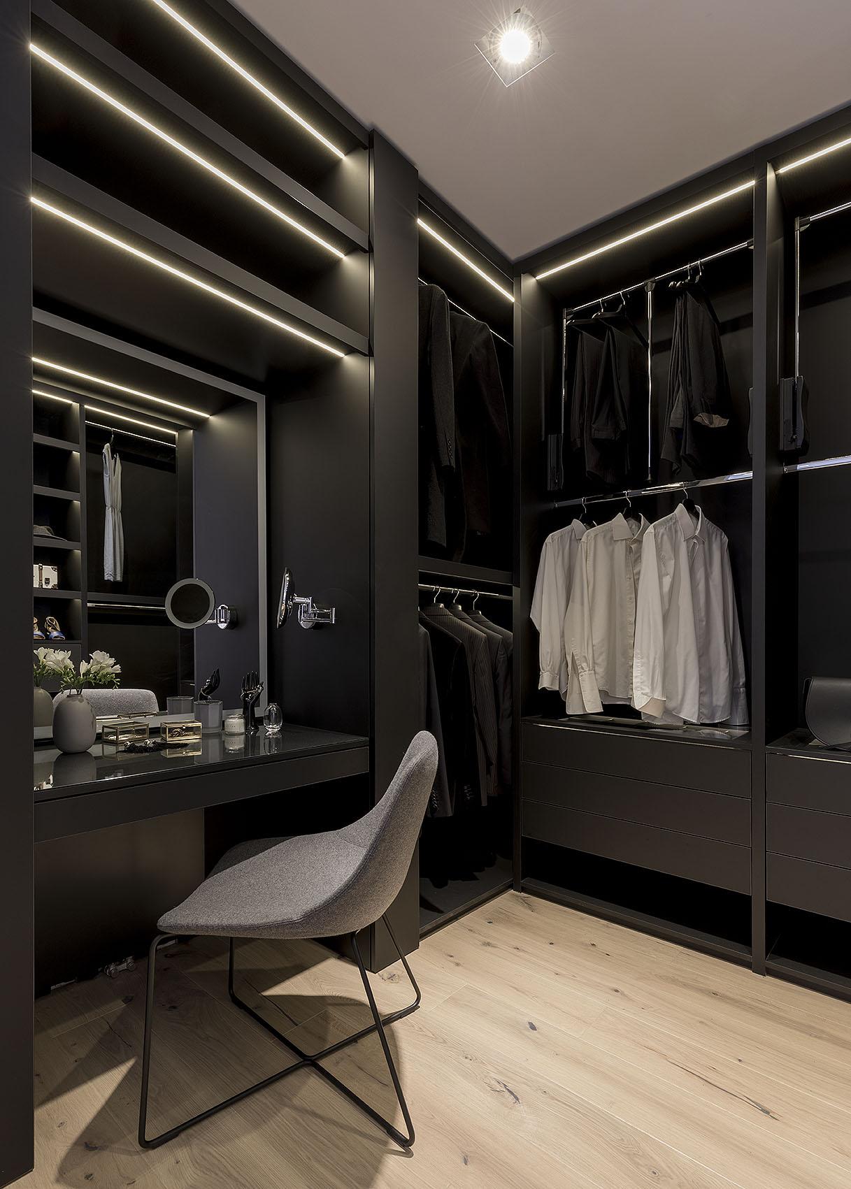 Garderoba na ubrania typu walk-in z toaletką, podświetlanym lustrem do makijażu.