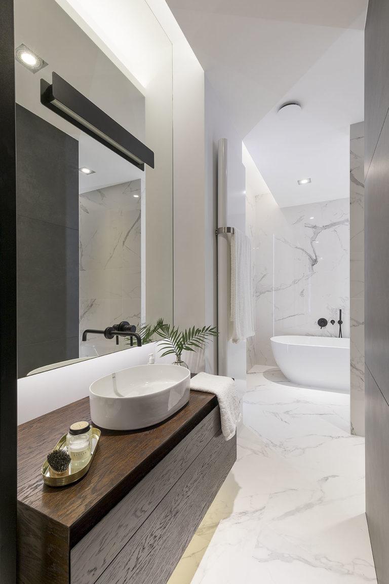 Widok na projekt łazienki z widoczną umywalką stawianą na blat oraz wanna wolnostojca.