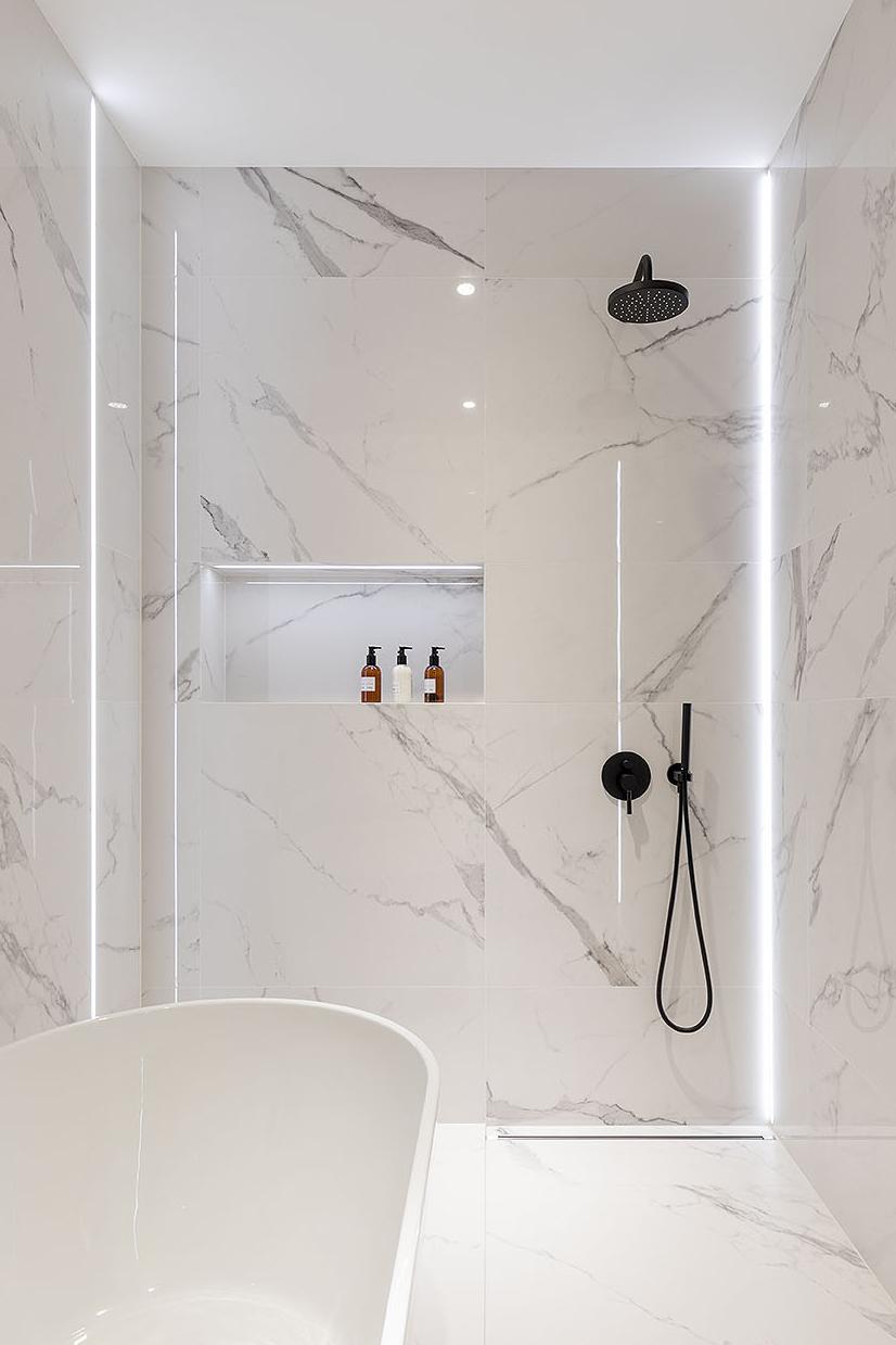Wnętrze łazienki z prysznicem typu walk-in, wanną oraz podtynkowy prysznic z deszczownicą.